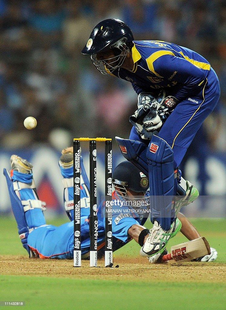 Indian cricketer Gautam Gambhir (L) dives to avoid being runout as Sri Lankan captain Kumar Sangakkara (R) looks on during the ICC Cricket World Cup 2011 Final match at The Wankhede Stadium in Mumbai on April 2, 2011.