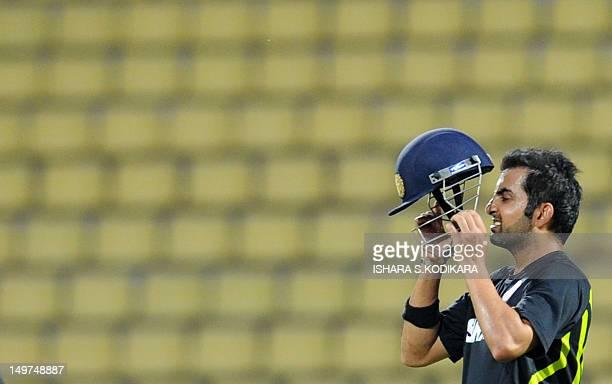 Indian cricketer Gautam Gambhir puts on his helmet during a practice session at the Pallekele International Cricket Stadium in Pallekele on August 3...