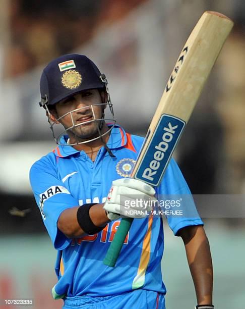 Indian cricketer Gautam Gambhir raises his bat after scoring a century during the third One Day International match between India and New Zealand at...