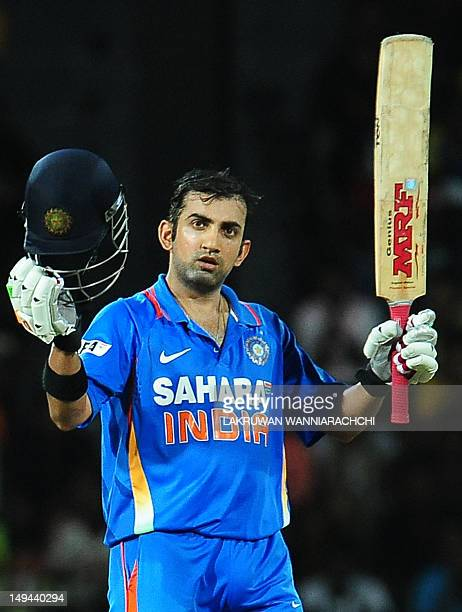 Indian cricketer Gautam Gambhir raises his bat and helmet in celebration after scoring a century during the third one day international match between...