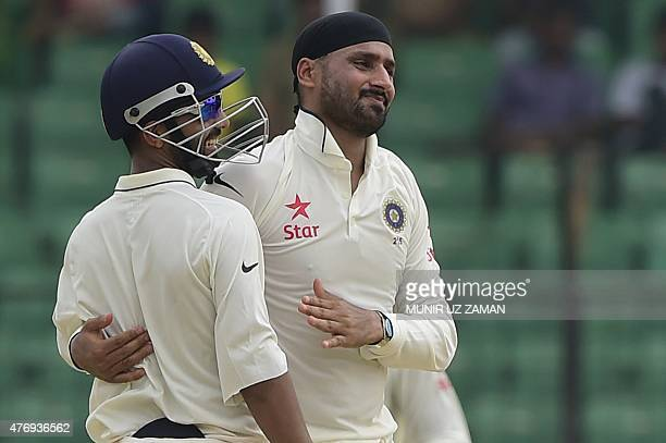 Indian cricketer Harbhajan Singh celebrates with teammate Ajinkya Rahane the dismissal of Bangladesh cricketer Mominul Haque during the fourth day of...