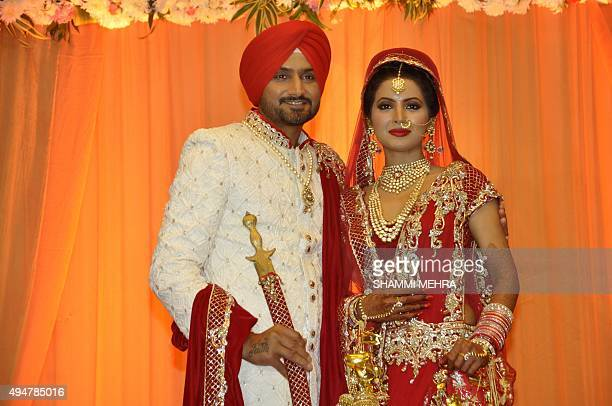 Indian cricketer Harbhajan Singh poses with his wife Geeta Basra during their marriage ceremony in Jalandhar on October 29 2015 / AFP PHOTO / SHAMMI...