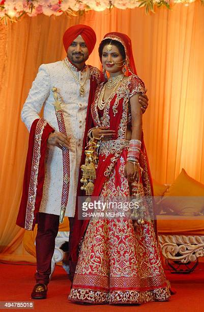 Indian cricketer Harbhajan Singh poses with his wife Geeta Basra during their marriage ceremony in Jalandhar on October 29 2015 AFP PHOTO/SHAMMI...