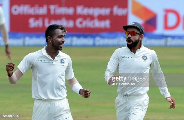 Indian cricketer Hardik Pandya celebrates with his captain Virat Kohli after he dismissed Sri Lankan cricketer Angelo Mathews during the second day...