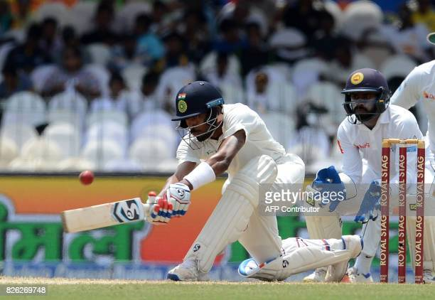 Indian cricketer Hardik Pandya is watched by Sri Lankan wicketkeeper Niroshan Dickwella as he plays a shot during the second day of the second Test...