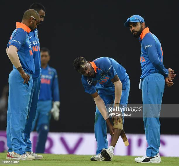 Indian cricketer Hardik Pandya reacts in pain after bowling a delivery during the second one day international cricket match between Sri Lanka and...