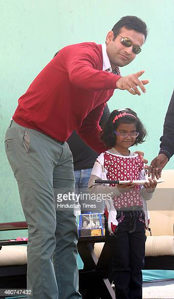 Indian cricketer Irfan Pathan with a student during celebration of sports carnival at Asnani School on December 21 2014 in Bhopal India
