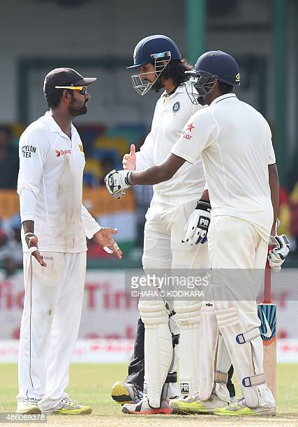 Indian cricketer Ishant Sharma and Sri Lankan cricketer Lahiru Thirimanne exchange words as Ravichandran Ashwin looks on during the fourth day of...