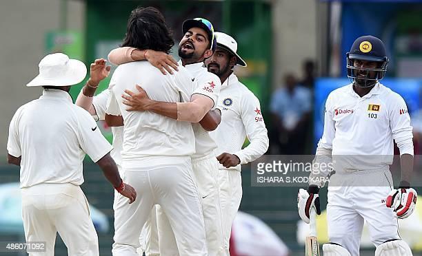 Indian cricketer Ishant Sharma and team captain Virat Kohli celebrate with teammates after dismissing Sri Lankan cricketer Upul Tharanga during the...