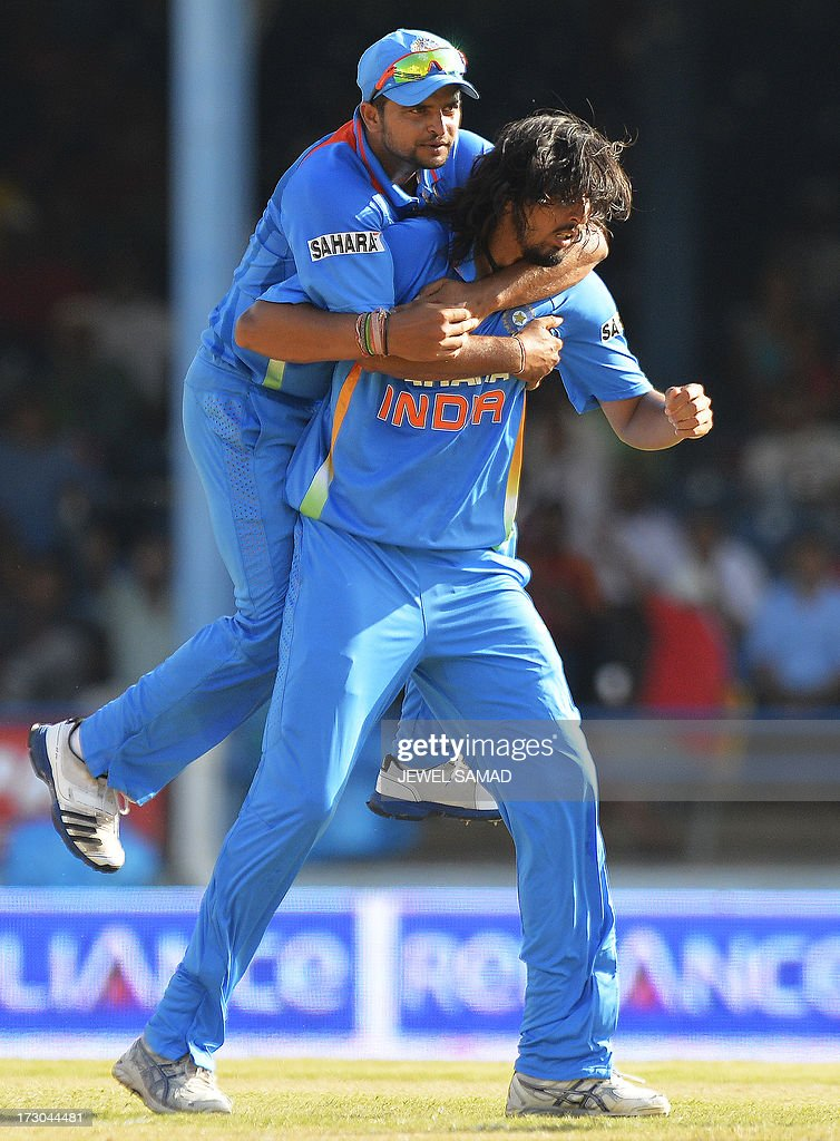 Indian cricketer Ishant Sharma (R) celebrates with teammate Suresh Raina after dismissing West Indies batsman Marlon Samuels during the fourth match of the Tri-Nation series between India and West Indies at the Queen's Park Oval in Port of Spain on July 5, 2013. India have scored 311/7 at the end of their innings. AFP PHOTO/Jewel Samad