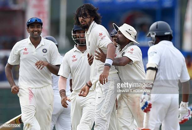 Indian cricketer Ishant Sharma celebrates with teammates after dismissing Sri Lankan cricketer Dinesh Chandimal during the fourth day of their third...