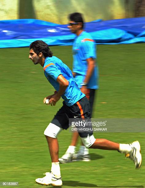 Indian cricketer Ishant Sharma runs to deliver the ball at the nets as team bowling coach Venkatesh Prasad looks on during a training session at...
