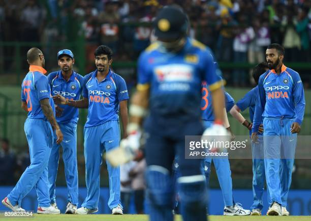 Indian cricketer Jasprit Bumrah celebrates with his teammates after he dismissed Sri Lankan cricketer Milinda Siriwardana during the third one day...