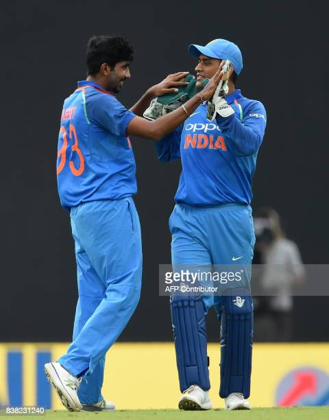 Indian cricketer Jasprit Bumrah celebrates with wicketkeeper Mahendra Singh Dhoni after he dismissed Sri Lankan cricketer Niroshan Dickwella during...