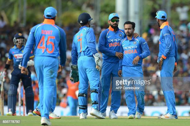 Indian cricketer Kedar Jadhav celebrates with his teammates after he dismissed Sri Lankan cricketer Niroshan Dickwella during the first One Day...