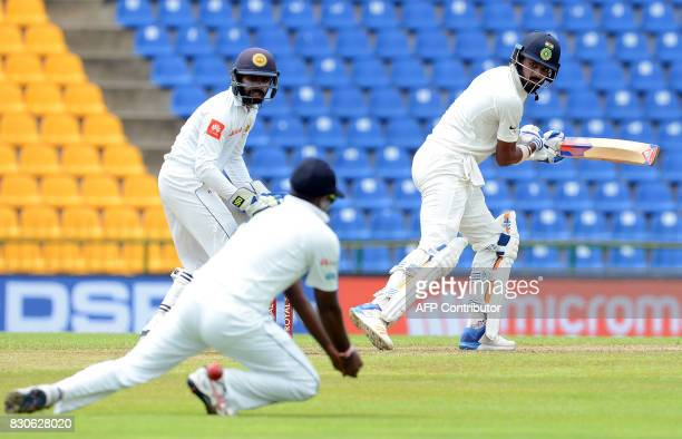 Indian cricketer Lokesh Rahul is watched by Sri Lankan wicketkeeper Niroshan Dickwella as he plays a shot during the first day of the third and final...