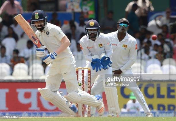 Indian cricketer Lokesh Rahul plays a shot as Sri Lankan wicketkeeper Niroshan Dickwella looks on during the first day of the second Test match...