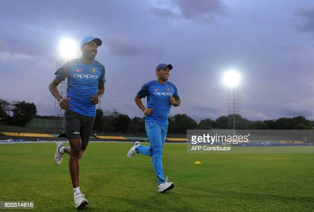 Indian cricketer Mahendra Singh Dhoni and Hardik Pandya warm up during a practice session at the Rangiri Dambulla International Cricket Stadium in...