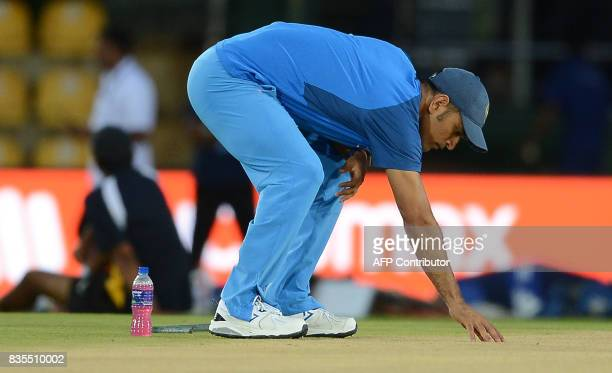 Indian cricketer Mahendra Singh Dhoni inspects the pitch during a practice session at the Rangiri Dambulla International Cricket Stadium in Dambulla...
