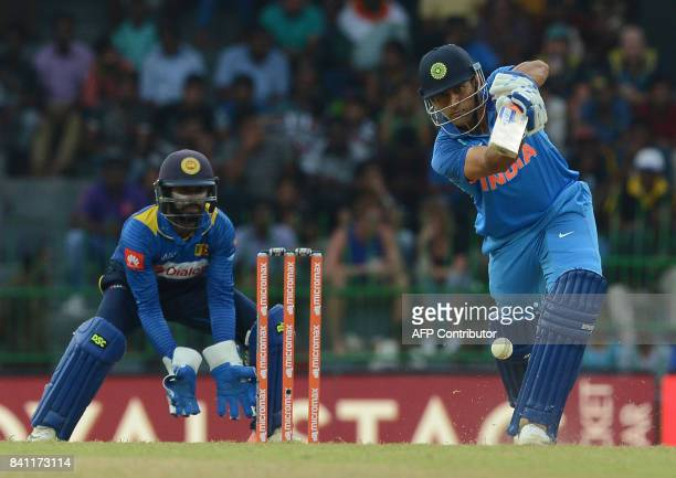 Indian cricketer Mahendra Singh Dhoni is watched by Sri Lankan wicketkeeper Niroshan Dickwella as he plays a shot during the fourth one day...