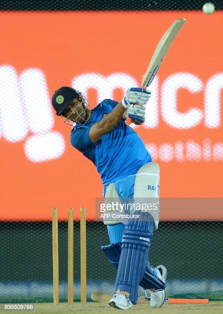 Indian cricketer Mahendra Singh Dhoni plays a shot during a practice session at the Rangiri Dambulla International Cricket Stadium in Dambulla on...