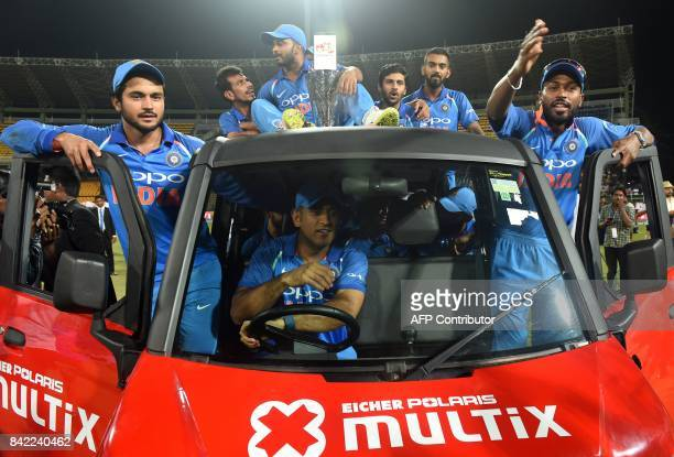 Indian cricketer Mahendra Singh Dhoni rides a vehicle carrying fellow team members and the winning trophy after their win over Sri Lanka in the fifth...