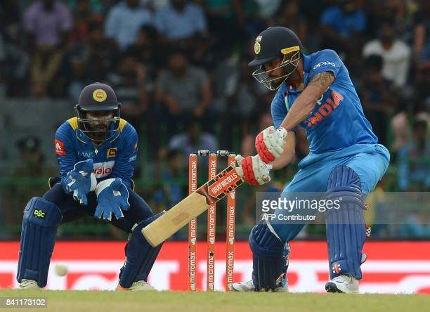Indian cricketer Manish Pandey is watched by Sri Lankan wicketkeeper Niroshan Dickwella as he plays a shot during the fourth one day international...