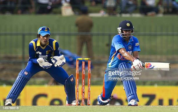 Indian cricketer Manoj Tiwary plays a shot as wicketkeeper Dinesh Chandimal reacts during the fifth and final oneday international match between Sri...