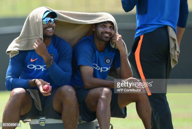 Indian cricketer Mohammed Shami speaks with teammates Umesh Yadav and Bhuvneshwar Kumar at a practice session at the Sinhalease Sports Club Ground in...