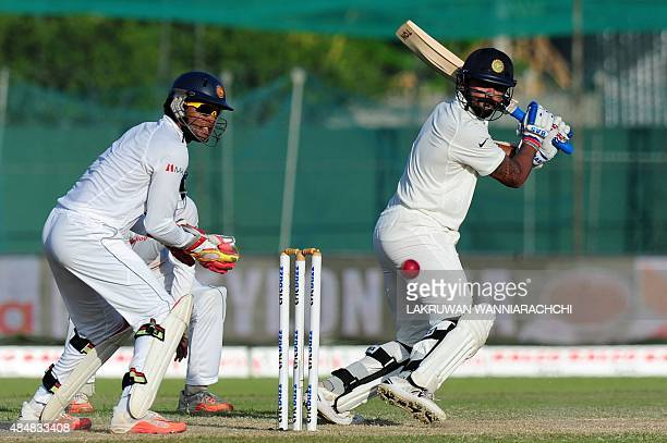 Indian cricketer Murali Vijay plays a shot as Sri Lankan wicketkeeper Dinesh Chandimal look on during the third day of the second Test cricket match...