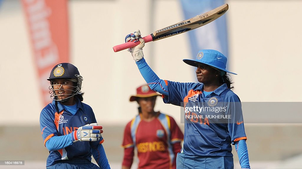 Indian cricketer Punam Raut (L) looks on as teammate Thirush Kamini raises her bat after reaching her half century (50 runs) during the inaugural match of the ICC Women's World Cup 2013 between India and West Indies at the Cricket Club of India's Brabourne stadium in Mumbai on January 31, 2013. Teams from Australia, England, New Zealand, Pakistan, South Africa, Sri Lanka, West Indies join hosts India for the global event which is being played from 31 January to 17 February. The women's World Cup opened in Mumbai with the cricketers hoping to put aside memories of the unsavoury build-up and gain their due recognition in a country where the men's game reigns supreme. AFP PHOTO/ Indranil MUKHERJEE