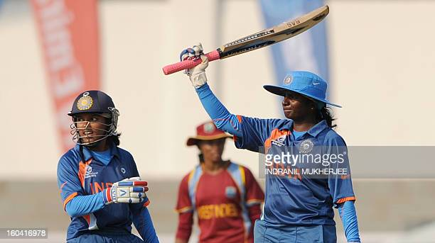 Indian cricketer Punam Raut looks on as teammate Thirush Kamini raises her bat after reaching her half century during the inaugural match of the ICC...