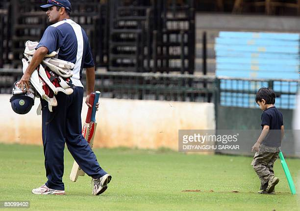 Indian cricketer Rahul Dravid walks with his batting gear as his son Samit Dravid follows him bat in hand during a training session at the...