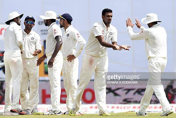 Indian cricketer Ravichandran Ashwin and teammates celebrate after dismissing Sri Lankan cricketer Lahiru Thirimanne during the third day of the...