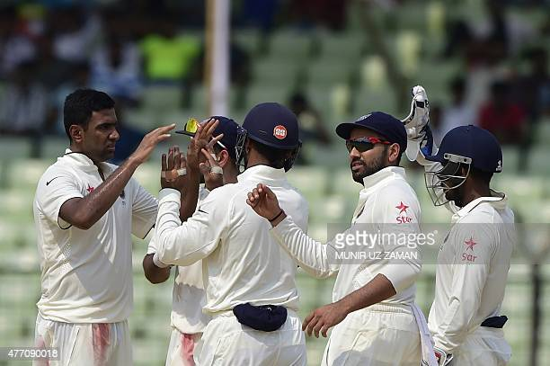 Indian cricketer Ravichandran Ashwin celebrates with his teammates after the dismissal of the Bangladesh cricketer Shuvagata Hom during the final day...