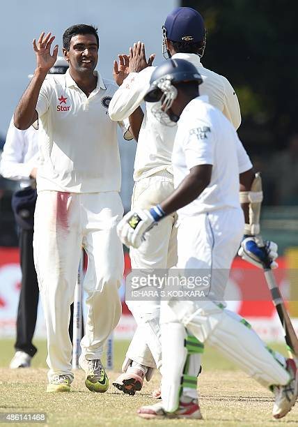 Indian cricketer Ravichandran Ashwin celebrates with teammates after dismissing Sri Lankan cricketer Rangana Herath during the final day of their...
