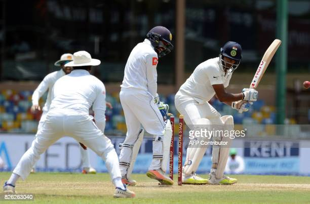 Indian cricketer Ravichandran Ashwin gets dismissed by Sri Lankan spinner Rangana Herath as wicketkeeper Niroshan Dickwella looks on during the...
