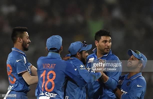 Indian cricketer Ravindra Jadeja celebrates with his teammates after the dismissal of the Pakistan cricketer Sarfraz Ahmed during the match between...