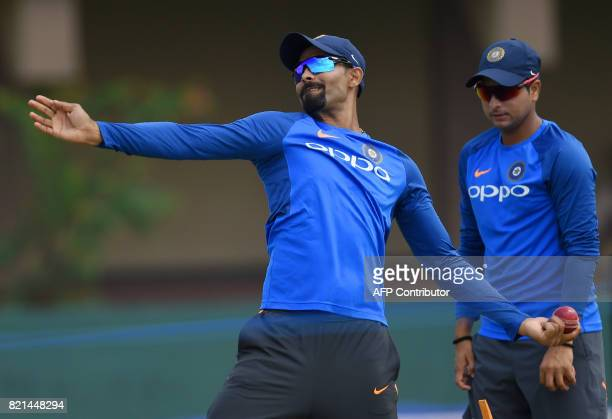 Indian cricketer Ravindra Jadeja delivers a ball as Kuldeep Yadav looks on during a practice session at Galle International Cricket Stadium in Galle...