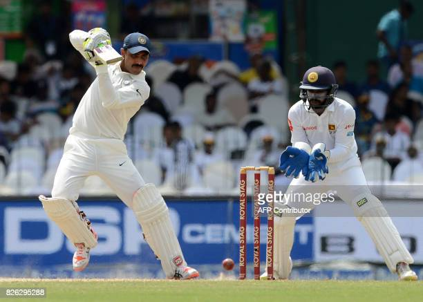 Indian cricketer Ravindra Jadeja is watched by Sri Lankan wicketkeeper Niroshan Dickwella as he plays a shot during the second day of the second Test...