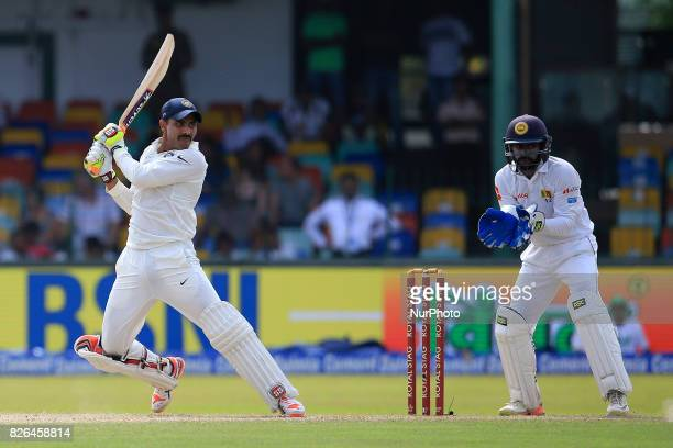 Indian cricketer Ravindra Jadeja plays a shot as Sri Lankan wicket keeper Niroshan Dickwella looks on during the 2nd Day's play in the 2nd Test match...