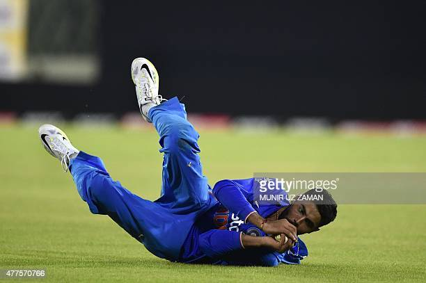 Indian cricketer Ravindra Jadeja takes the catch to dismiss Bangladesh cricketer Nasir Hossain during the first One Day International cricket match...