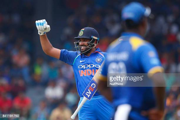 Indian cricketer Rohit Sharma celebrates after scoring 100 runs during the 4th One Day International cricket match between Sri Lanka and India at the...