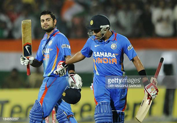 Indian cricketer Rohit Sharma congratulates teammate Virat Kohli for scoring a century during the second One Day International match between Indian...