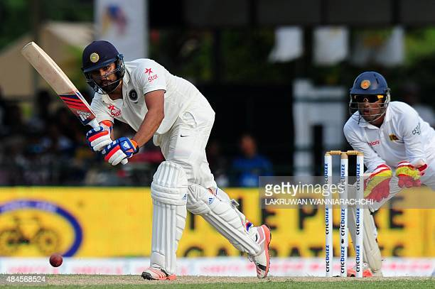 Indian cricketer Rohit Sharma plays a shot as Sri Lankan wicketkeeper Dinesh Chandimal look on during the opening day of their second test match...