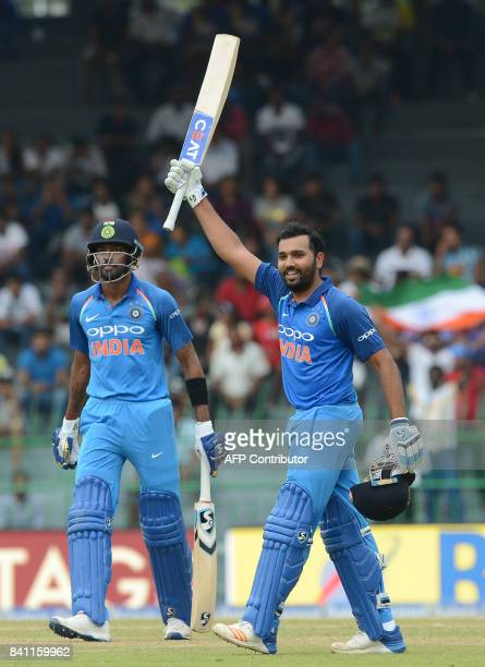Indian cricketer Rohit Sharma raises his bat after he scored a century as his teammate Hardik Pandya look on during the fourth one day international...