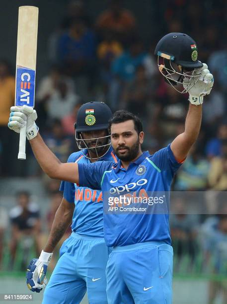 Indian cricketer Rohit Sharma raises his bat and helmet in celebration after scoring a century as his teammate Hardik Pandya look on during the...