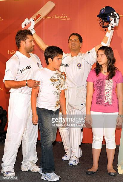 Indian cricketer Sachin Tendulkar along with his son Arjun and daughter Sara pose with his waxwork figure at the unveiling ceremony in Mumbai on...