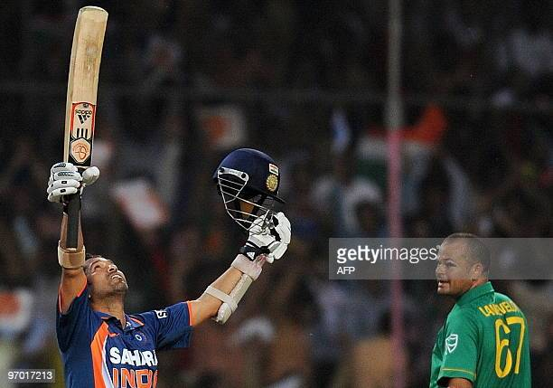 Indian cricketer Sachin Tendulkar celebrates scoring a world record breaking double century during the second One Day International cricket match at...