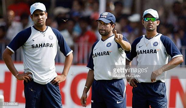 Indian cricketer Sachin Tendulkar gestures as teammates Rohit Sharma and Dinesh Karthick look on during a training session at Reliance Cricket...